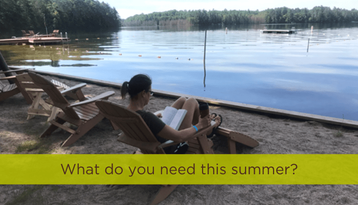 Darcy relaxing by a lake, reading a book, summer self care, titled what do you need this summer