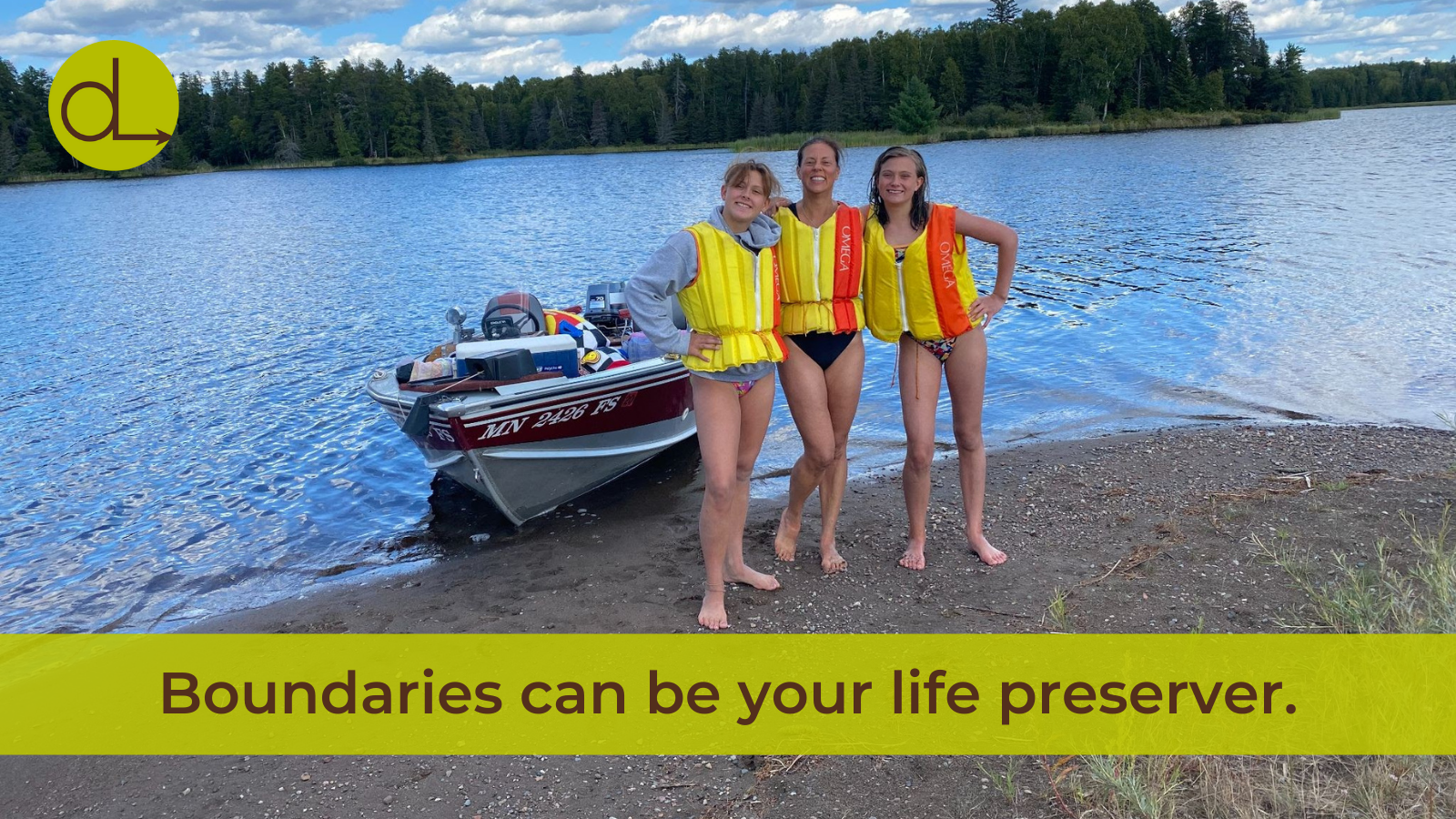 Photo of Darcy with her two daughters posing for a photo in front of a boat on a lake, wearing lifejackets.